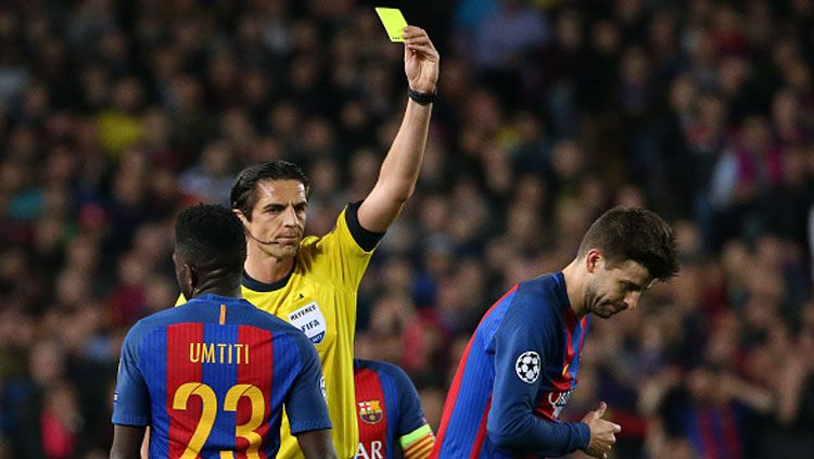 Wasit asal Jerman, Deniz Aytekin, memberi kartu kuning kepada Gerard Pique. Copyright: © Jean Catuffe/Getty Images