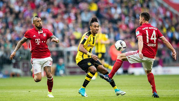 Aubameyang mencoba melepaskan diri dari hadangan pemain Munchen. Copyright: © Boris Streubel/Getty Images