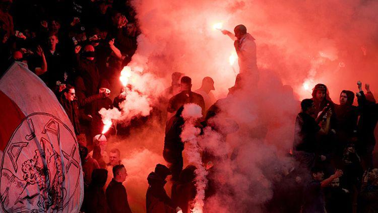 Fans Ajax Amsterdam menyalakan flare di dalam stadion. Copyright: © OLAF KRAAK/AFP/Getty Images
