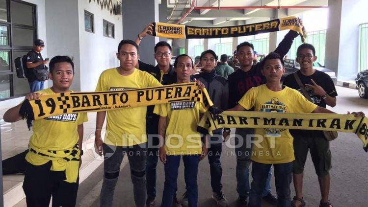Komunitas penggemar klub Barito Putera atau disebut Barito Mania, turun ke jalanan untuk menyerahkan bantuan logistik kepada masyarakat yang terdampak banjir. Copyright: © Muhammad Adi Yaksa/Indosport