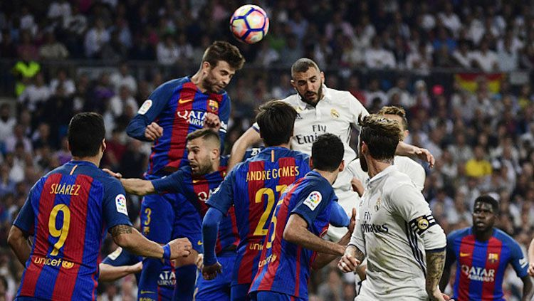 Bek Barcelona Gerard Pique (atas kiri) mengepalai bola dengan pemain Real Madrid Karim Benzema Copyright: © PIERRE-PHILIPPE MARCOU/AFP/Getty Image