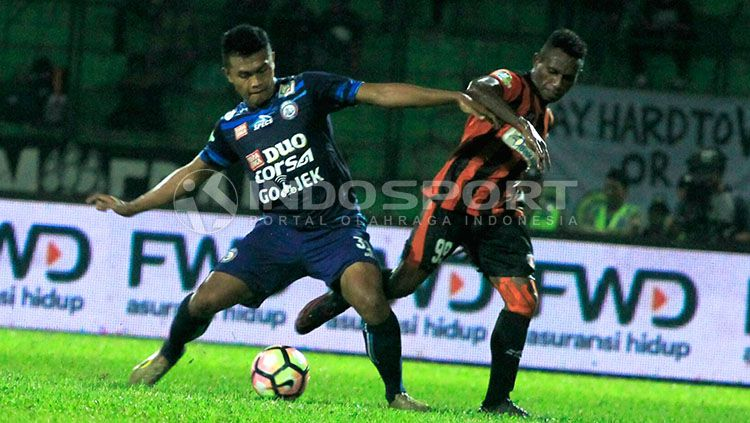Bek kiri Arema, Junda Irawan saat berebut bola dengan Mariando Uropmabin Copyright: © Indosport/Ian Setiawan
