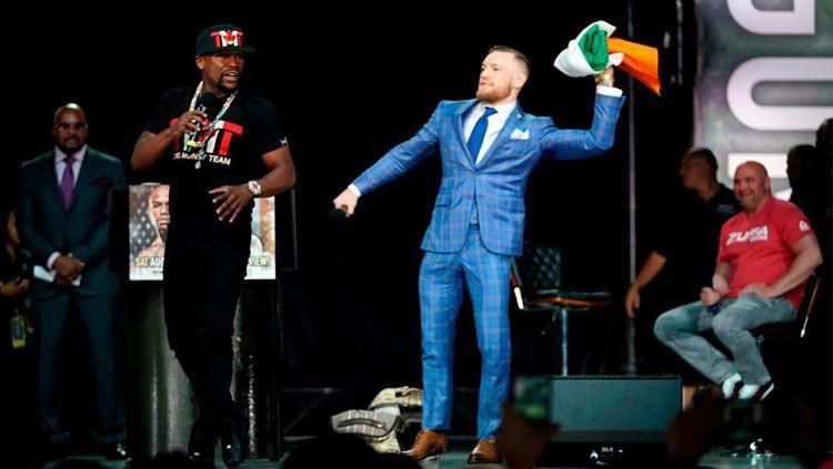 Conor McGregor melempar bendera Irlandia ke wajah Floyd Mayweather. Copyright: © The Sun