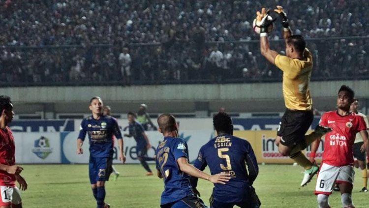 Andritany Ardhiyasa berhasil mengamankan bola dari serangan Persib Bandung. Copyright: © @kumparan