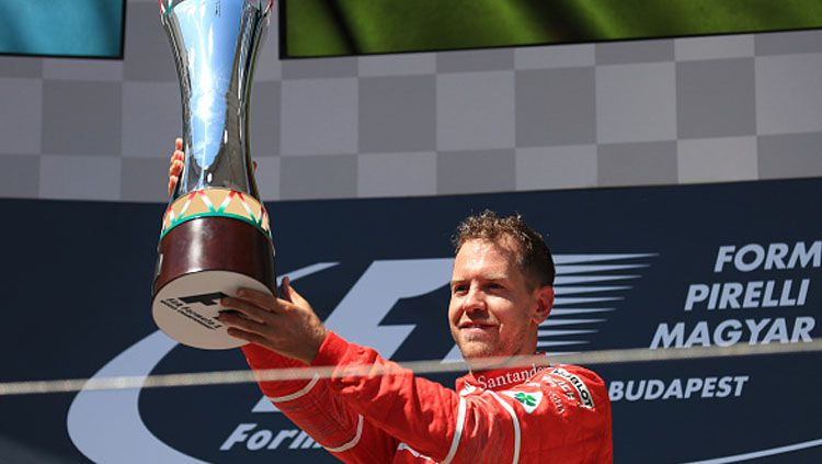 Sebastian Vettel menunjukan trofi diatas podium. Copyright: © INDOSPORT