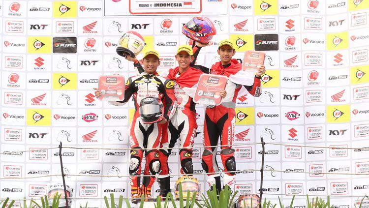 Gerry Salim (tengah) dan Andi Gilang (kanan) saat berpose bersama Rheza Danica. Copyright: © Astra Honda Racing Team