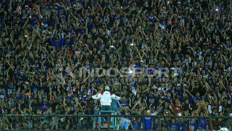Aksi Aremania saat memberi dukungan kepara Arema FC. Copyright: © Indosport/Ian Setiawan