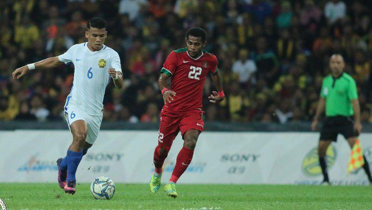Yabes Roni Malaifani dampingi pemain Malaysia saat menggiring bola. Copyright: © twitter@FAM_Malaysia