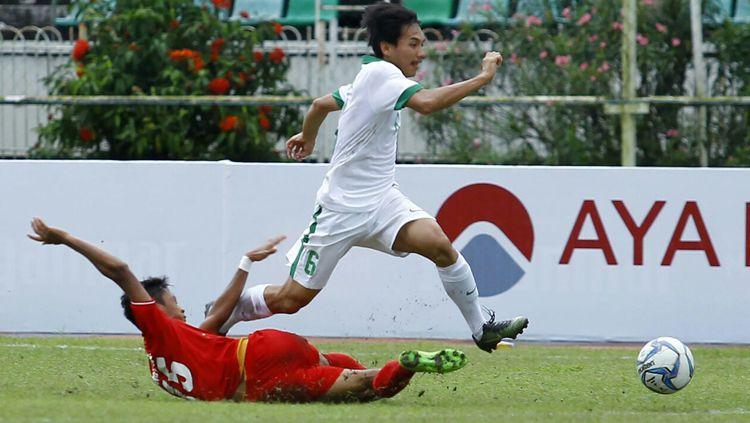 Muhammad Iqbal berhasil melewati pemain Myanmar. Copyright: © PSSI
