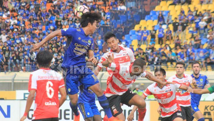 Duel udara Pemain Persib Bandung melawan Madura United. Copyright: © Arif Rahman/INDOSPORT