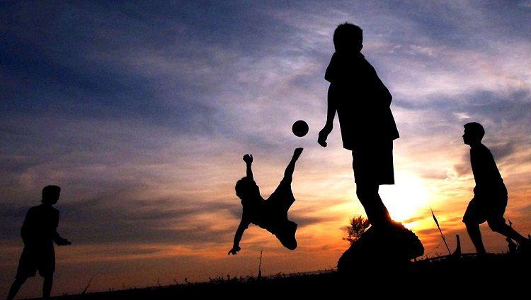 Anak-anak Papua bermain bola di balik senja Copyright: © Internet