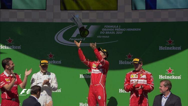 Sebastian Vettel melempar piala juara GP Brasil. Copyright: © Twitter/@F1