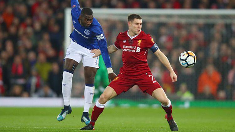 James Milner (kanan) berebut bola dengan pemain Everton. Copyright: © Getty Images