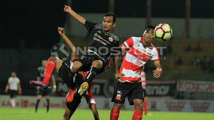 Riko Simanjuntak dibuat terbang untuk menghindari kawalan ketat pemain Madura United. Copyright: © Ian Setiawan/INDOSPORT