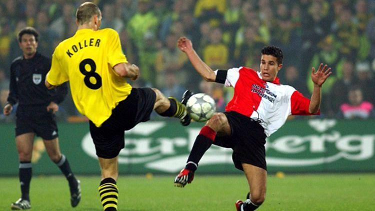 Robi van Persie (kiri) sedang berebut bola dengan pemian Dortmund, Jan Koller. Copyright: © Getty Images