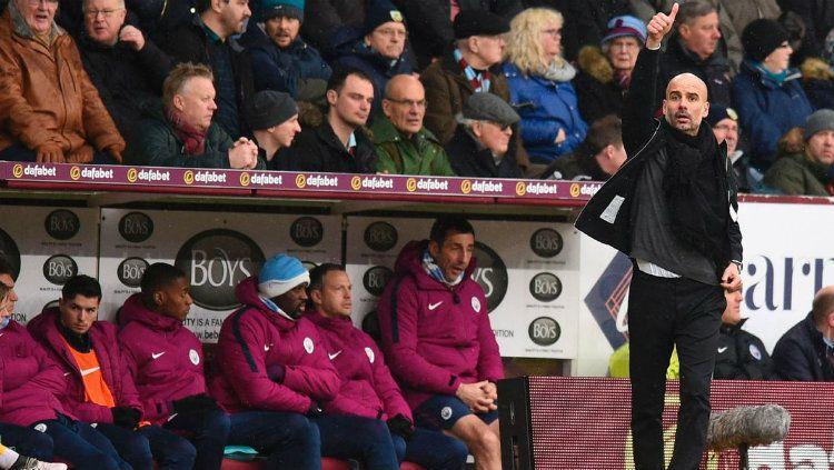 Manajer Manchester City Pep Guardiola saat memberikan instruksi kepada anak asuhnya di pinggir lapangan. Copyright: © INDOSPORT