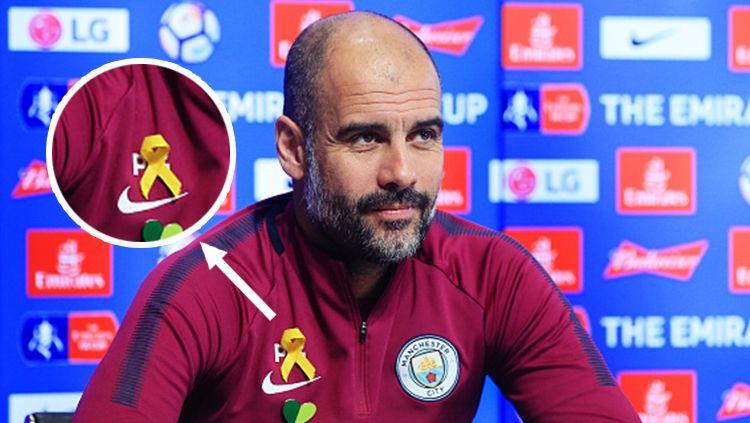 Pep Guardiola saat bertemu dengan awak media dengan memakai pita kuning di bagian dada. Copyright: © Getty Images