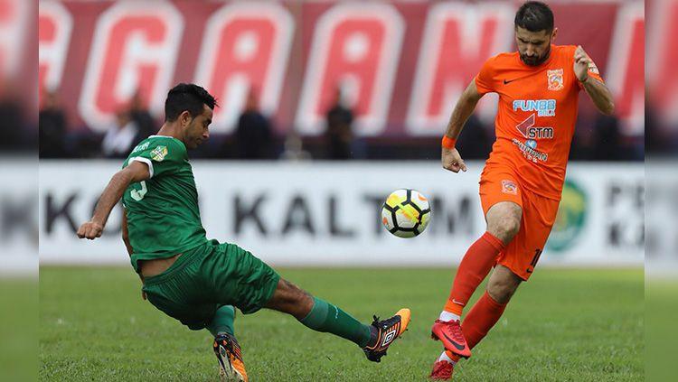 Otavio Dutra (kiri) mencoba menghentikan pergerakan Srdjan Lopicic (kanan). Copyright: © Twitter Boneo FC