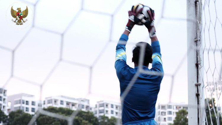 Satria Tama menangkap bola dalam sesi latihan di Singapura. Copyright: © PSSI