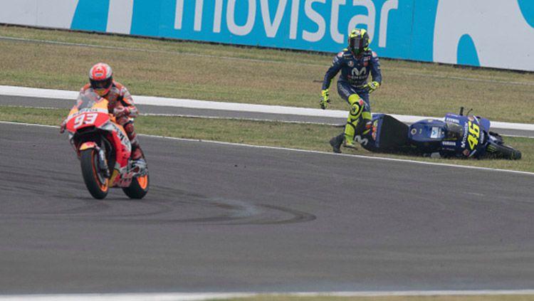 Valentino Rossi tampak melihat ke arah Marc Marquez yang melaju usai kecelakaan. Copyright: © INDOSPORT