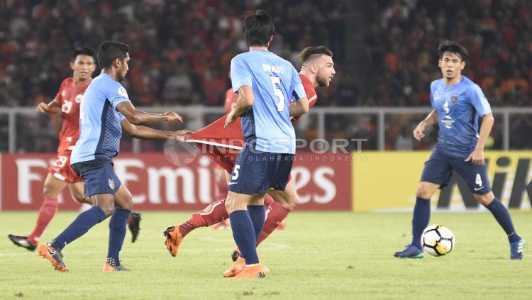 Marko Simic mendapatkan tarikan dibajunya saat menggiring bola. Copyright: © Herry Ibrahim/INDOSPORT