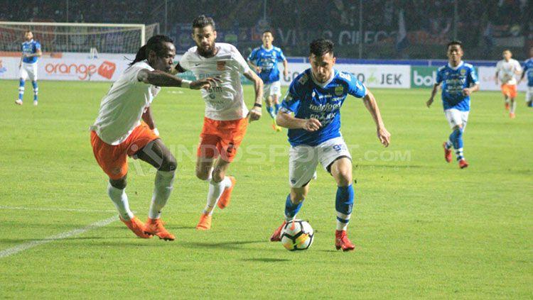 Jonathan Bauman tengah mengontrol bola dan dikawal ketat dua pemain Borneo FC. Copyright: © Aarif Rahman/INDOSPORT