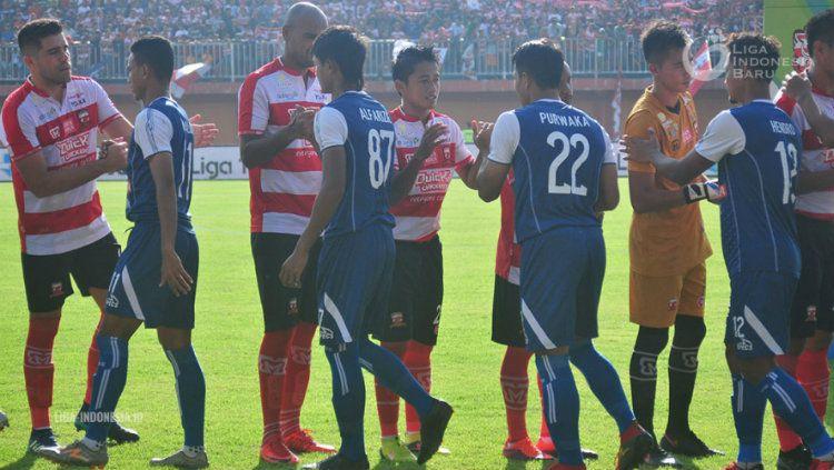 Para pemain Arema dan Madura saling bersalaman sebelum pertandingan mulai. Copyright: © liga-indonesia.id