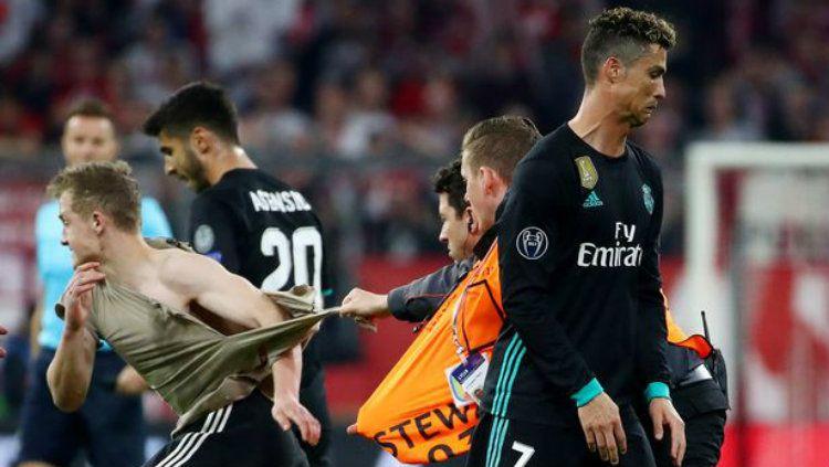 Suporter yang masuk lapangan di laga Munchen vs Madrid. Copyright: © Reuters