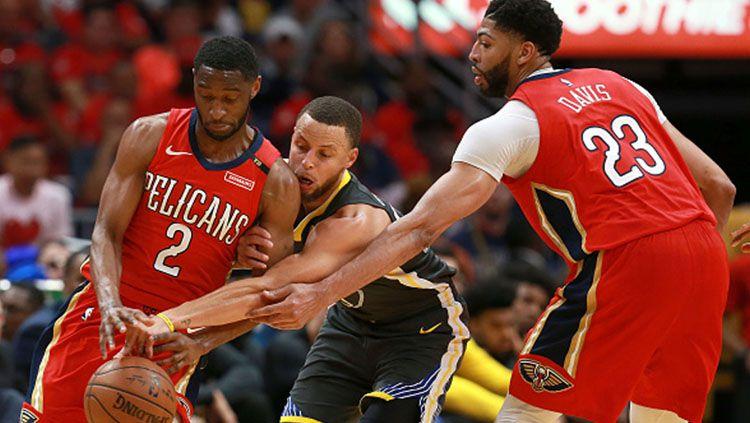 Stephen Curry (tengah) tampak tidak berkutik di hadang dua pemain New Orleans Pelicans sekaligus. Copyright: © INDOSPORT