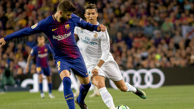 Gerard Pique (kiri) menjaga penguasaan bola dari kejaran Ronaldo. Copyright: © INDOSPORT