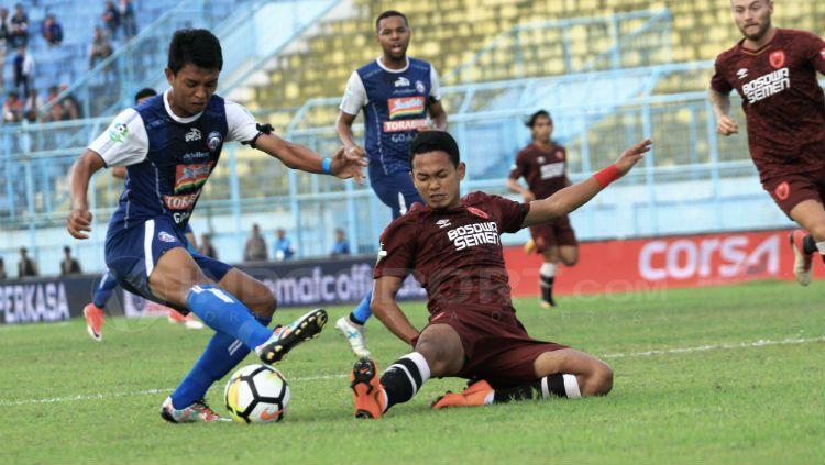 Dedik Setiawan berusaha menjaga bola dari penggawa PSM Copyright: © Ian Setiawan/INDOSPORT