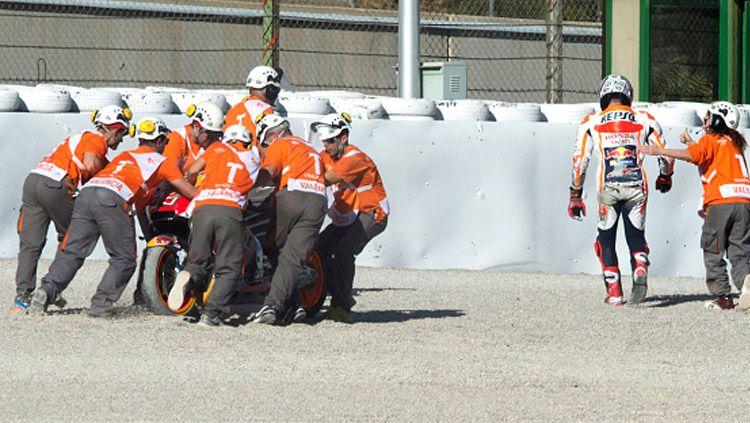 Marc Marquez saat mendapat pertolongan usai terjatuh. Copyright: © INDOSPORT