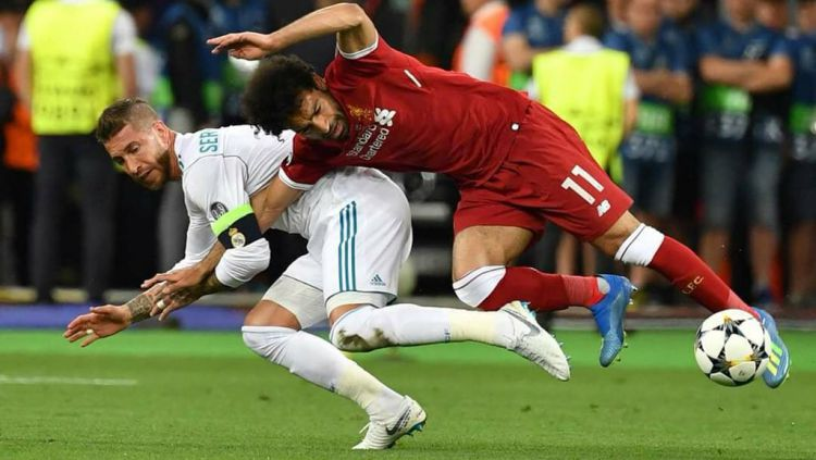 Sergio Ramos menarik tangan Mohamed Salah. Copyright: © Getty Images