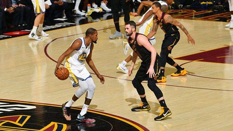 Kevin Durant tengah membawa bola dan berusaha melewati pemain Cleveland Cavaliers. Copyright: © Getty Images