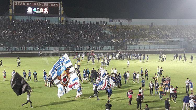 Invasi Aremania ke lapangan pasca laga kontra Bhayangkara FC berbuntut sanksi denda. Copyright: © Ian Setiawan/INDOSPORT