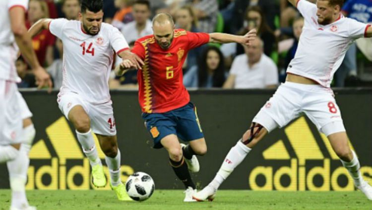 Andres Iniesta saat membawa bola mendapat gangguan dari pemain Tunisia. Copyright: © Getty Images