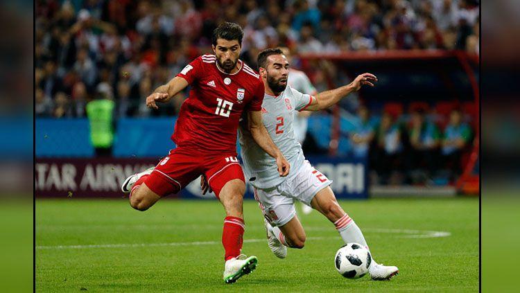 Bek Timnas Spanyol, Dani Carvajal (kanan) saat berduel dengan pemain Iran, Ansarifard. Copyright: © Getty Images