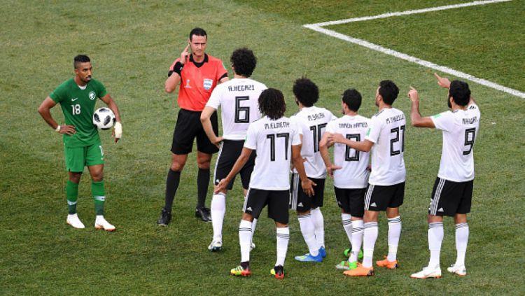 Para pemain Mesir melakukan protes kepada wasit, yang berujung penalti untuk Arab Saudi. Copyright: © Getty Images