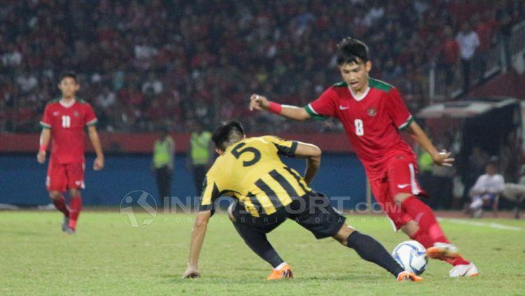 Witan Sulaiman memalingkan bola dari serangan pemain Malaysia. Copyright: © Fitra Herdian/Indosport