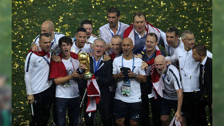 Ekspresi kegembiraan Didier Deschamps dan staf pelatih Timnas Prancis sambil memegang trofi Piala Dunia. Copyright: © Getty Images