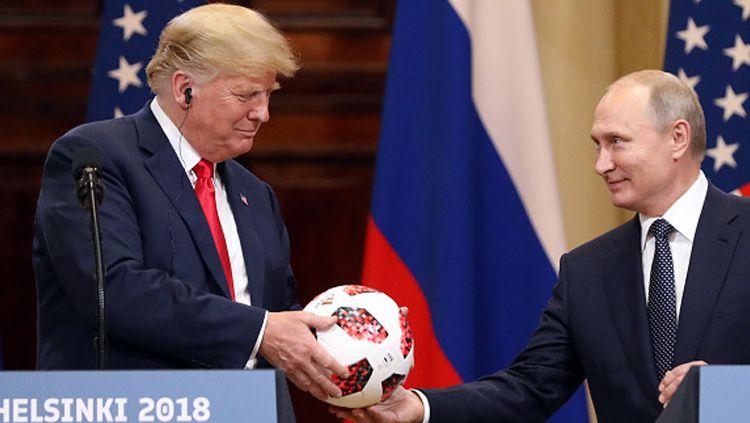 Usai gelar Piala Dunia 2018, Presiden Rusia, Vladimir Putin (kanan) berikan sebuah bola ke Presiden Amerika Serikat, Donald Trump. Copyright: © Getty Images