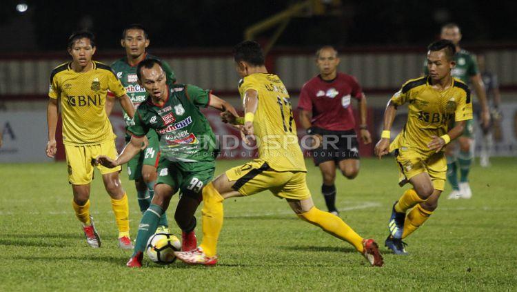 Rachmad Hidayat (hijau) dikawal ketat pemain Bhayangkara FC. Copyright: © Herry Ibrahim/INDOSPORT