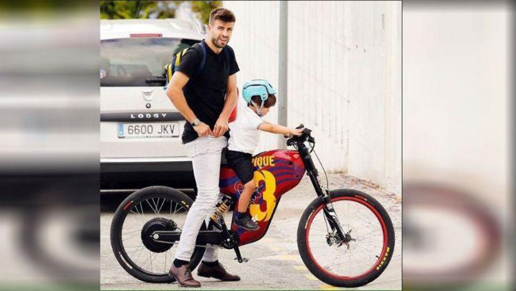 Gerard Pique saat mengantar anaknya menggunakan sepeda. Copyright: © Istimewa