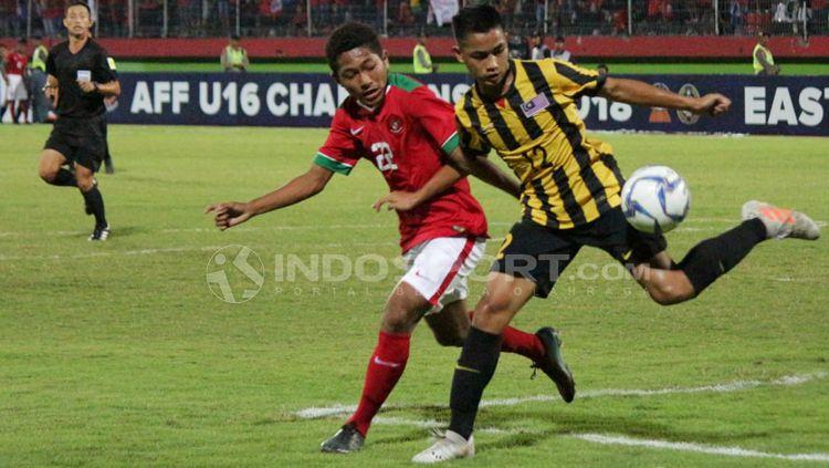 Muhammad Fajar menghalau pemain Malaysia untuk mengambil bola. Copyright: © Fitra Herdian/Indosport