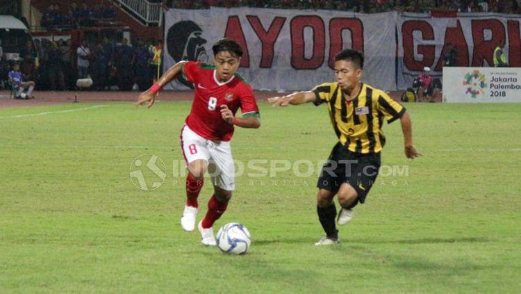 Sutan Zico tengah mengejar bola bersama pemain Malaysia. Copyright: © Fitra Herdian/Indosport