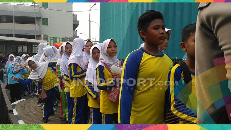 Anak sekolah SDN Kayuringin Jaya 11 mengantri di pintu masuk. Copyright: © Petrus Manus Da' Yerimon/INDOSPORT