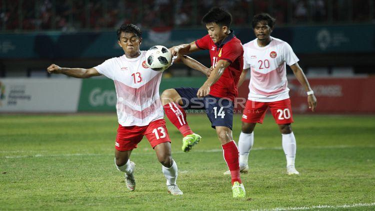Febri Hariyadi berusaha merebut bola dari kaki pemain Laos. Copyright: © INDOSPORT/Herry Ibrahim
