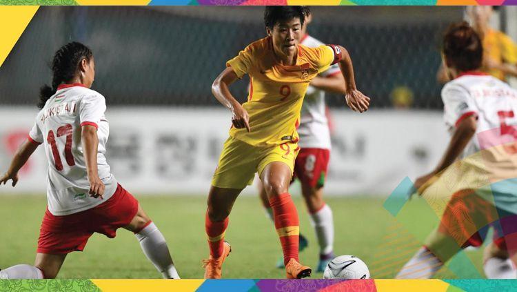 Pemain timnas Cina putri (kuning) membawa bola dan dikawal ketat pemain Tajikistan. Copyright: © AFC