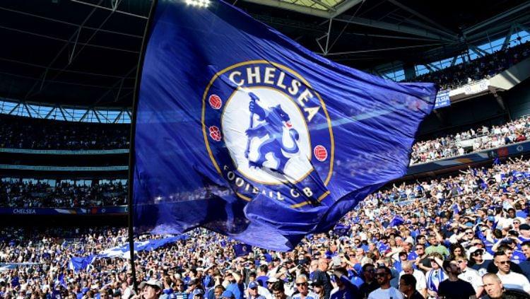 Pendukung Chelsea mengibarkan bendera berlogo klub. Copyright: © INDOSPORT