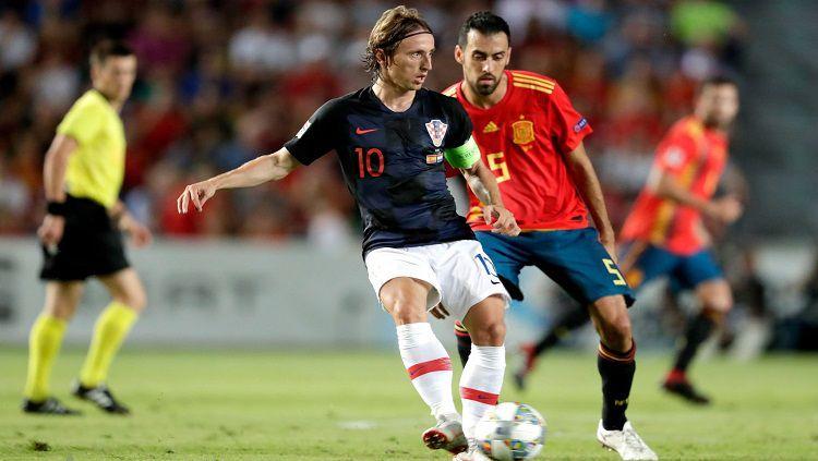 Luka Modric (kiri) sedang menguasai bola dalam pertandingan melawan Spanyol. Copyright: © twitter @BarcaTimes